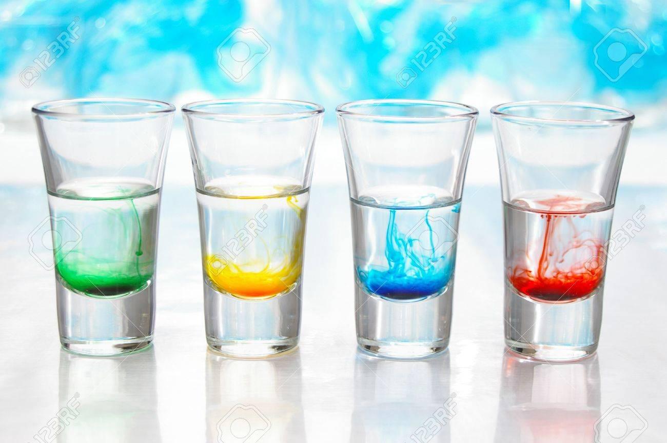 442138-tourbillons-de-couleur-lumineux-mélange-avec-de-l-eau-dans-les-flacons-de-verre-clair-